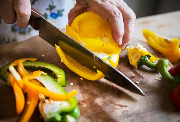 Woman cutting bell pepper on a cutting board