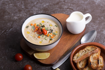 Lentil soup puree with bacon in a bowl on a dark wooden background