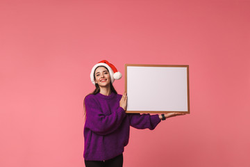 Beautiful happy young emotional woman posing isolated over pink background holding copyspace blank.