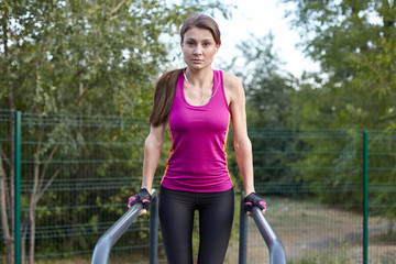 Young caucasian woman with unusual face workouts on the park sports ground. Pulling up on the horizontal bar, bright sportswear. White earphones, protective gloves. Morning training. Outdoors