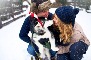 Family portrait of cute happy couple hugging with their alaskan malamute dog licking man's face. Funny puppy wearing santa christmas deer antlers and kissing woman. Freedom lifestyle pet lovers.