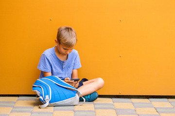 Boy with smartphone sitting on the ground near colorful wall