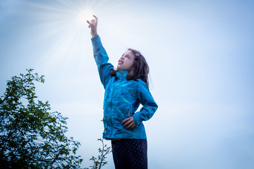 Outdoor portrait of young girl in blue jacket reaching her arm in the air to catch the sun.