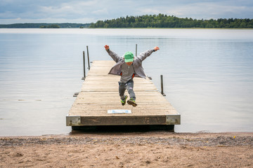 Front view of a young boy running  on a jetty and jumps in air towards a beach.