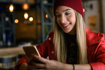 Beautiful urban girl using smart-phone out in the café club texting and vlogging.