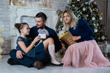 Christmas photo of happy family with gift boxes on background of decorated Christmas tree. Family celebrates New year