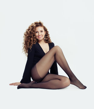 Sexy woman fashion model with beautiful legs in black tights on white background