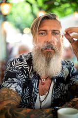 Attraktiver bärtiger Hipster raucht in einem Coffeeshop