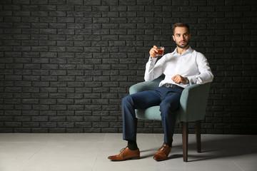 Young businessman drinking whiskey near dark brick wall
