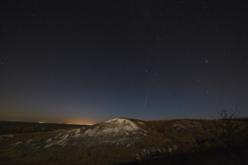 Night sky with stars and a meteorite over the hills. The landscape was photographed on a long exposure.