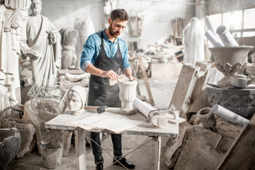 Man in blue t-shirt and apron working in the old atmospheric studio brushing stone vase on the table