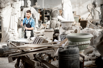 Sculptor working at the atmospheric old workshop with sculptures and trash