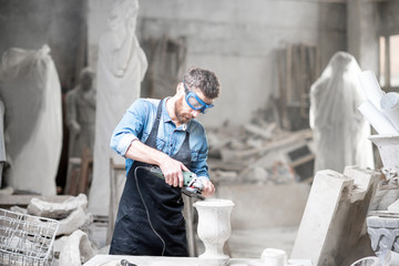 Sculptor in workware grinding stone vase at the working space in the old atmospheric studio