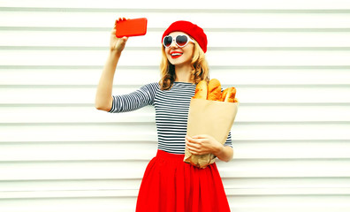 Cheerful smiling young woman taking selfie picture by smartphone holding paper bag with long white bread baguette on white wall background