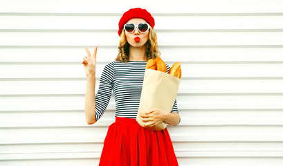 Portrait pretty cool girl wearing french red beret holding paper bag with long white bread baguette on white wall background Wall mural