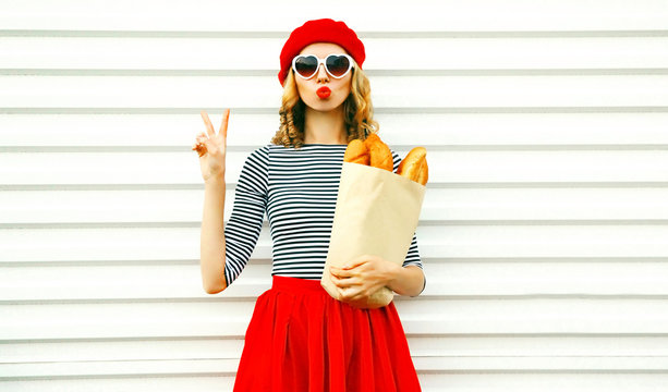 Portrait pretty cool girl wearing french red beret holding paper bag with long white bread baguette on white wall background