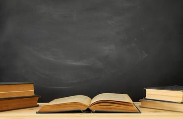 stack of books over wooden desk in front of blackboard.