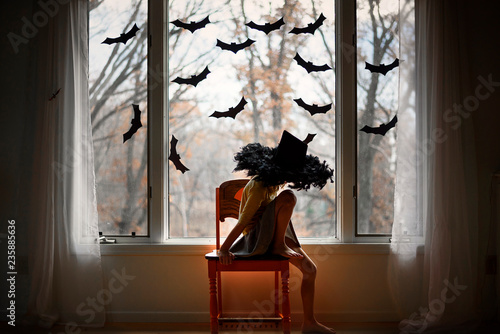 Girl wearing hat sitting on chair by window