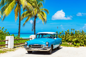 Fotorollo Bekannte Orte in Amerika Amerikanischer blauer Oldtimer parkt vor dem Strand in Varadero Cuba - Serie Cuba Reportage
