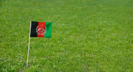 Afghanistan flag. Photo of Afghanistan flag on a green grass lawn background. Close up of national flag waving outdoors.