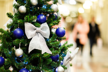 Image of decorated Christmas spruce with white and blue balls in store .