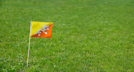 Bhutan flag. Photo of Bhutanese flag on a green grass lawn background. Close up of national flag waving outdoors.