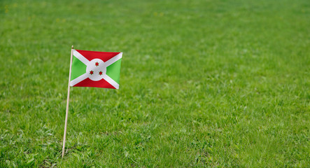 Burundi flag. Photo of Burundi flag on a green grass lawn background. Close up of national flag waving outdoors.