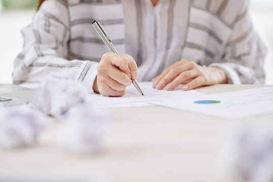 Faceless view of woman in blouse writing on paper document sitting at desk in office