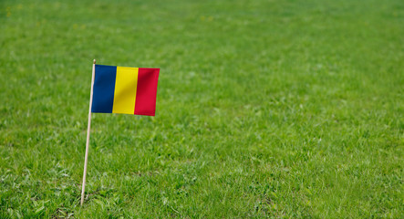 Chad flag. Photo of  Chad flag on a green grass lawn background. Close up of national flag waving outdoors.
