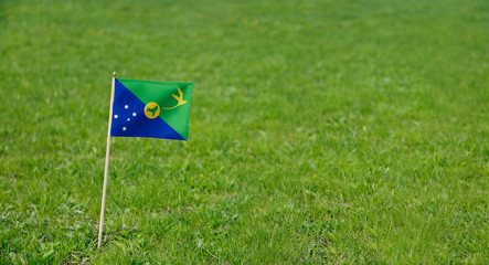 Christmas Island flag. Photo of Christmas Island flag on a green grass lawn background. Close up of national flag waving outdoors.