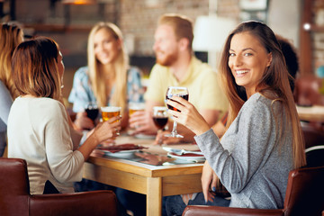 Woman looking at camera and holding glass of wine while sitting in restaurant. In background friends drinking and chatting.