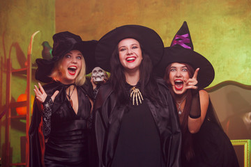 Photo of screaming three young witches in black hats