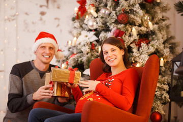 Photo of man in Santa hat with gift and pregnant woman