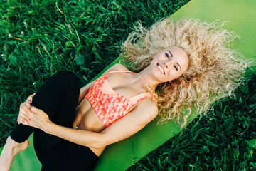 Image of young curly woman lying on sport rug in park