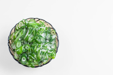 green onions frozen on a  platter on a white background