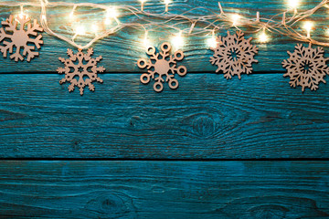 Image of blue wooden table with burning New Year garland, snowflakes.