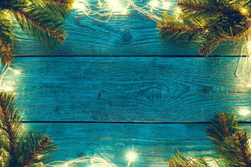 Photo of blue wooden surface with burning New Year's garland around perimeter, with branches of spruce