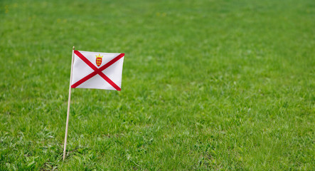 Jersey flag. Photo of Jersey flag on a green grass lawn background. Close up of national flag waving outdoors.