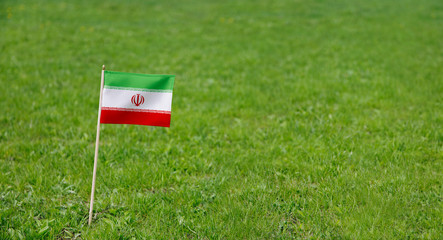 Iran flag. Photo of Iranian flag on a green grass lawn background. Close up of national flag waving outdoors.
