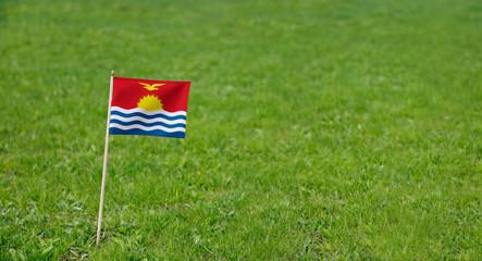 Kiribati flag. Photo of Kiribati flag on a green grass lawn background. Close up of national flag waving outdoors.