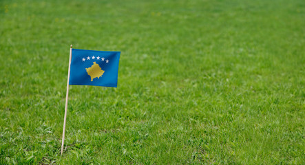 Kosovo flag. Photo of  Kosovo flag on a green grass lawn background. Close up of national flag waving outdoors.