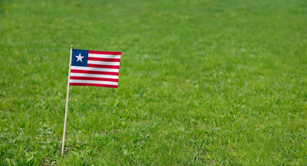 Liberia flag. Photo of Liberian flag on a green grass lawn background. Close up of national flag waving outdoors.