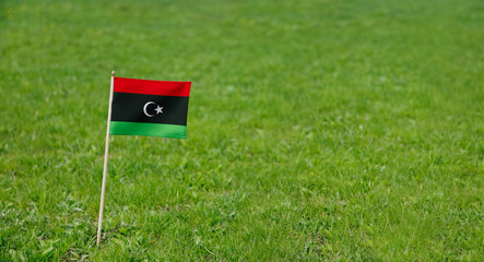 Libya flag. Photo of Libya flag on a green grass lawn background. Close up of national flag waving outdoors.