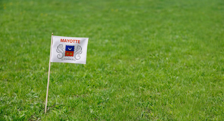 Mayotte flag. Photo of Mayotte flag on a green grass lawn background. Close up of national flag waving outdoors.