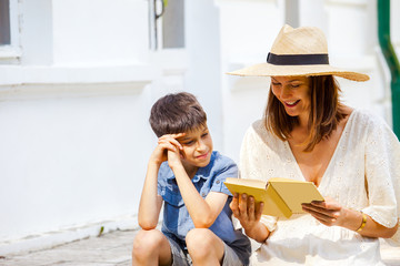 woman reading a funny book to a boy