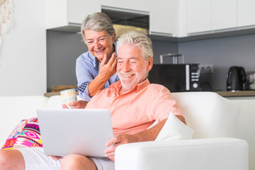 aged senior caucasiann couple sit down on couch using an internet device connected laptop together having fun and smiling - retired life for man and woman old people at home enjoying lifestyle