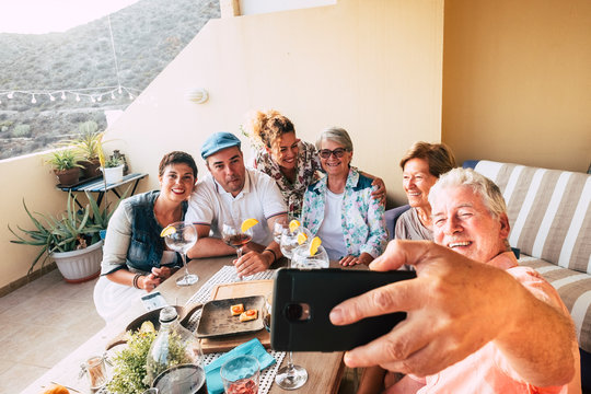 group of friends have fun together celebrating and dining at home in the outdoor terrace with smile and laugh - man take a slefie picture with phone - friendship and family concept for mixed people