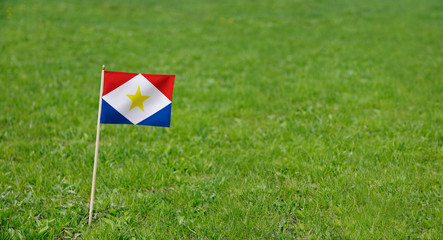Saba flag. Photo of Saba flag on a green grass lawn background. Close up of national flag waving outdoors.