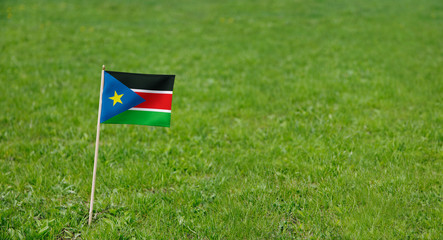 South Sudan flag. Photo of South Sudan flag on a green grass lawn background. Close up of national flag waving outdoors.