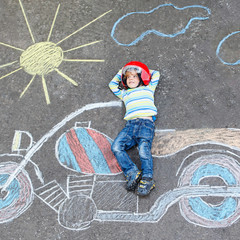 Creative leisure for children: Funny little child of four years in helmet having fun with motorcycle picture drawing with colorful chalks. Children, lifestyle, fun concept